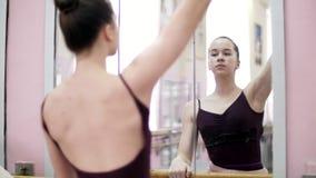 I danskorridor utför den unga ballerina i svart body lutningsplie, flyttande händer elegantly som står den near barren på arkivfilmer