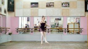 I danskorridor utför den unga ballerina i svart body pascourruen, pointe, henne flyttar sig till och med balettgruppen arkivfilmer