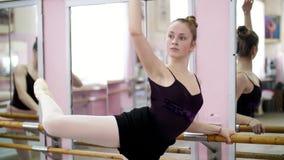 I danskorridor utför den unga ballerina i svart body piruett elegantly och att stå den near barren på spegeln i balett lager videofilmer