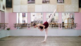 I danskorridor utför den unga ballerina i svart body storslagen battementbaksida, lyfter upp hennes ben bakom elegantly, in stock video