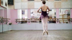 I danskorridor utför den unga ballerina i svart body turnerar chaines, henne som elegantly flyttar sig till och med balettgruppen stock video
