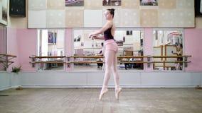 I danskorridor utför den unga ballerina i svart body turnerar chaines, henne som elegantly flyttar sig till och med balettgruppen arkivfilmer