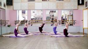 I danskorridor utför unga ballerina i purpurfärgade body den delde behå I 3 positionen med framåt lutande, flickor är arkivfilmer