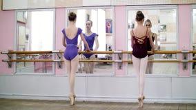 I danskorridor utför unga ballerina i purpurfärgade body developpe åt sidan på pointeskor, lyfter upp deras ben stock video