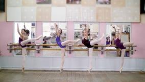 I danskorridor utför unga ballerina i purpurfärgade body developpeinställning utplånar på pointeskor, lyfter deras ben lager videofilmer