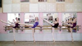 I danskorridor utför unga ballerina i purpurfärgade body inställning utplånar på pointeskor som står den near barren på arkivfilmer