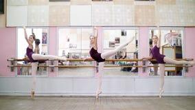 I danskorridor utför unga ballerina i purpurfärgade body storslagen battementbaksida på pointeskor, lyfter upp deras ben lager videofilmer