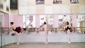 I danskorridor utför unga ballerina i svarta body storslagen battementbaksida på barren, elegantly som, nära står arkivfilmer
