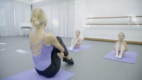 I dansstudio korrigerar lagledaren position av att sitta för små flickor stock video