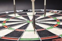I dardi delle frecce colpiscono l'obiettivo e sono indicati sul nero Fotografie Stock