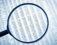 I dati finanziari vedono attraverso la lente della lente di ingrandimento sul giornale finanziario Fotografia Stock