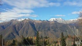 I de Kaukasus bergen, snömaxima, den blåa himlen och molnen Fotografering för Bildbyråer