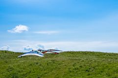 I deltaplani hanno parcheggiato prima della presa del volo sopra le colline un giorno soleggiato Fotografie Stock