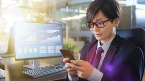 I den östliga asiatiska affärsmannen Uses Smartphone som för kontor skriver rackarungen royaltyfri bild