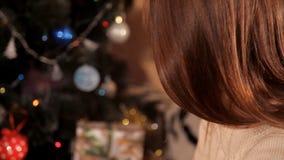 I den festliga miljön för ` s för det nya året nära julgranen blåser flickan ut stearinljusen stock video