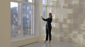 I den ljusa studiounga flickan som står det near fönstret och talar vid den videopd appellen på minnestavlan som diskuterar om pr stock video