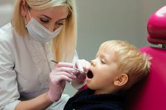 I denti del bambino d'esame del dentista alla clinica dentaria fotografie stock