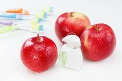 I denti dentari floss, spazzolino da denti e mela rossa fotografia stock