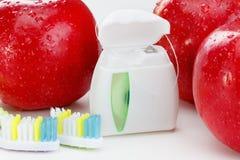 I denti dentari floss, spazzolino da denti e mela rossa su fondo bianco immagine stock libera da diritti