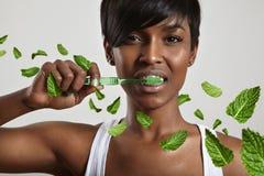 I denti di pulizia della donna di bellezza hanno circondato i leavs della menta Immagine Stock