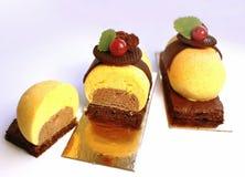 I dessert variopinti del cioccolato e dell'arancia con il ribes rosso e la decorazione del cooke del cioccolato, hanno affettato fotografie stock