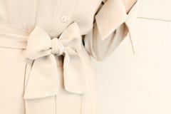 I dettagli del legame della cinghia dell'arco in donna beige vestono lo stile dell'attrezzatura Modo d'avanguardia Immagini Stock