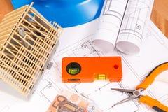 I diagrammi elettrici, strumenti del lavoro per i lavori dell'ingegnere, alloggiano in costruzione e valute euro sullo scrittorio Immagine Stock Libera da Diritti