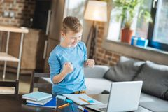 Cheerful nice boy saying yes. I did it. Cheerful pleasant nice boy smiling and saying yes while finishing his school project Stock Photos