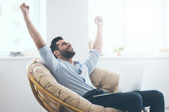 I did it!. Handsome young man keeping arms raised and looking happy while sitting in a big comfortable chair at home with laptop laying on his knees Royalty Free Stock Photo