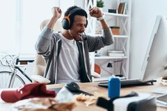 I did it!. Happy young man in casual clothing gesturing and smiling while spending time at home stock image