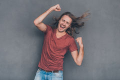 I did it!. Happy young man in casual wear standing against grey background and gesturing Stock Photos