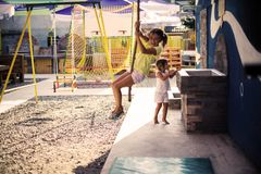 I did it and I happy. Little girl climbing up the rope in playground. Space for copy stock image