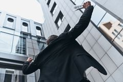 I did it!. Low angle rear view of young man in full suit gesturing while standing outdoors stock image