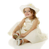 I Did It Myself. An adorable, dressed-up 2-year-old happy with her accomplishment as she finishes putting on her own shoes.  On a white background Stock Images
