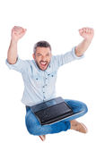 I did it!. Top view of happy young man in casual wear keeping arms raised while sitting on the floor and with laptop while being isolated on white background Royalty Free Stock Photo