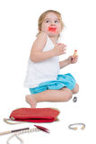 I didnt do it. Fun concept with a naughty little girl with her mouth smeared with lipstick surrounded by her mothers scattered cosmetics looking upwards with a Royalty Free Stock Photos