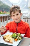 I dieci anni di ragazzo sta mangiando in caffè della montagna Fotografie Stock