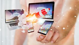 I dispositivi di collegamento di tecnologia dell'uomo d'affari ed il razzo startup 3D rendono Immagine Stock