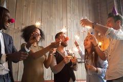 I diversi amici felici che celebrano la vigilia del nuovo anno fanno festa insieme dentro Fotografia Stock