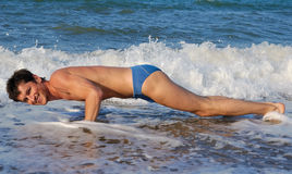 I do my morning exercise. A man performing exercises on a beach stock photo