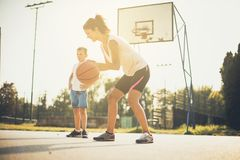 I do not participate in the game anymore. Mother and son playing basketball stock images