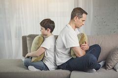Sad parent and kid keeping resentful silence. I do not talk with you anymore. Upset men and boy turning back to each other while situating on couch. They are Royalty Free Stock Photography