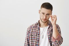 I do not trust you. Attractive trendy european guy with beard taking off eyewear and looking from under forehead at. Camera with serious and confident Stock Photo