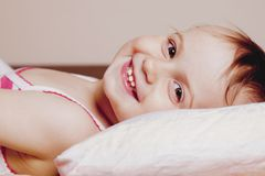 I do not want to sleep yet.Cute active little child girl having fun in bed and doesn`t want going to fall asleep.  royalty free stock photos