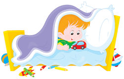 I do not want to sleep. Little boy playing with a toy car under a blanket in his bed Royalty Free Stock Image