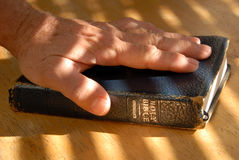 I Do Solemnly Swear. Hand On Well Used Old Bible Under Painted Light Stock Photos