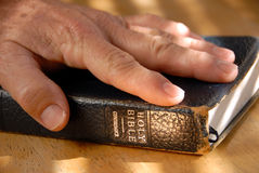 I Do Solemnly Swear. Hand On Well Used Old Bible Under Painted Light Stock Photography