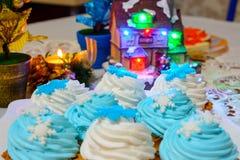 I dolci e le candele della crema di Natale si chiudono su sulla tavola con le luci colorate Fotografia Stock