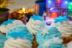 I dolci e le candele della crema di Natale si chiudono su sulla tavola con le luci colorate Immagine Stock