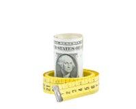 I dollari acciambellati dentro il nastro della misura su fondo bianco, concetto per l'affare e risparmiano i soldi immagini stock libere da diritti